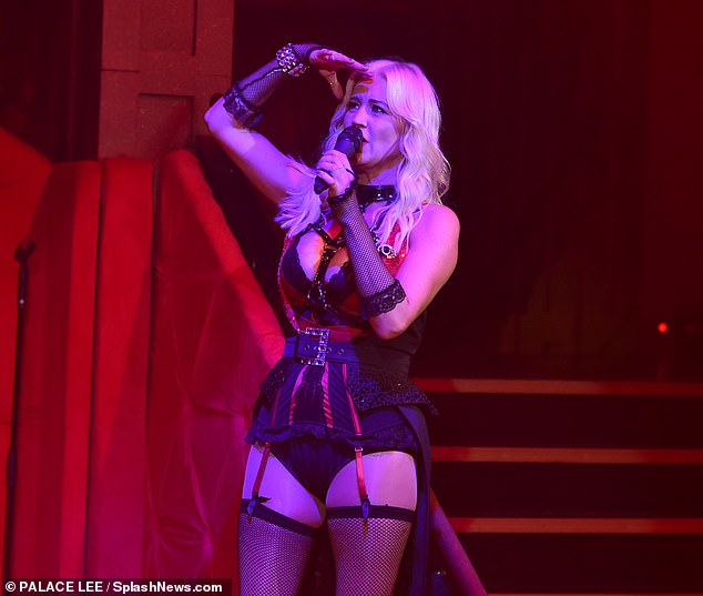 Racy: The singer completed the racy costume with a leather studded choker that set pulses racing as it clipped onto the centre of her plunging shapewear