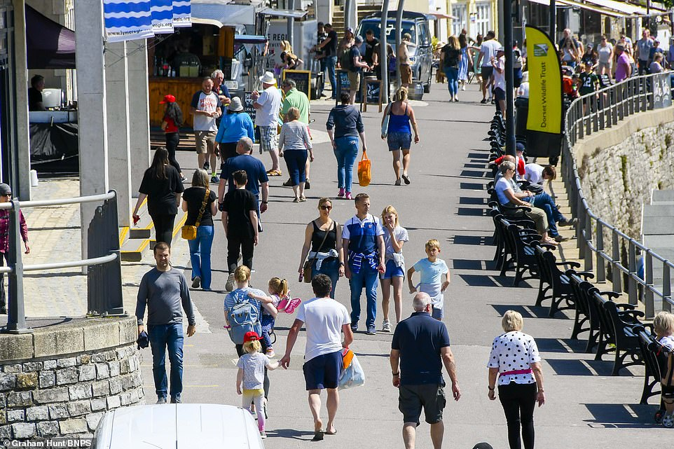People arrive to the seaside resort of Lyme Regis in Dorset today as the country enjoys rising temperatures