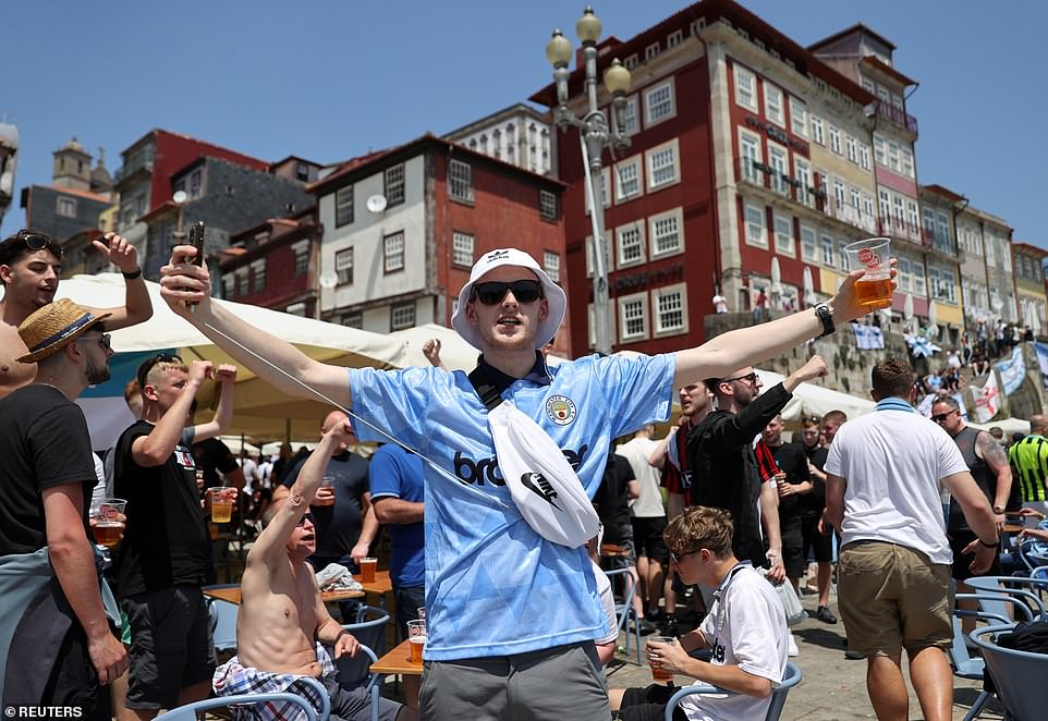 A Manchester City fan, with a pint in hand smiles for a photograph as he holds hi mobile phone aloft on Saturday afternoon