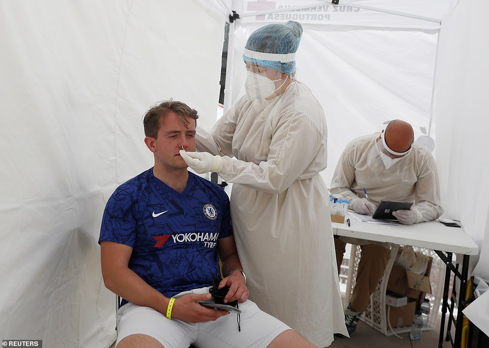 A young Chelsea fan gets tested for the coronavirus by medics ahead of the match on Saturday night