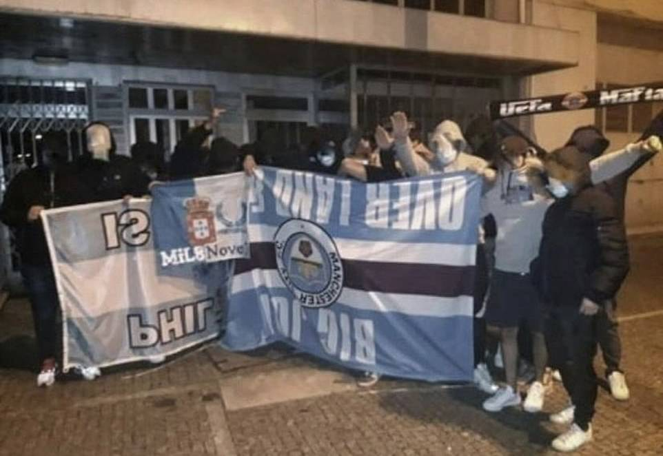Masked Porto fans hold up a stolen Manchester City flag during the proceedings to the Champions League final in the Portuguese city