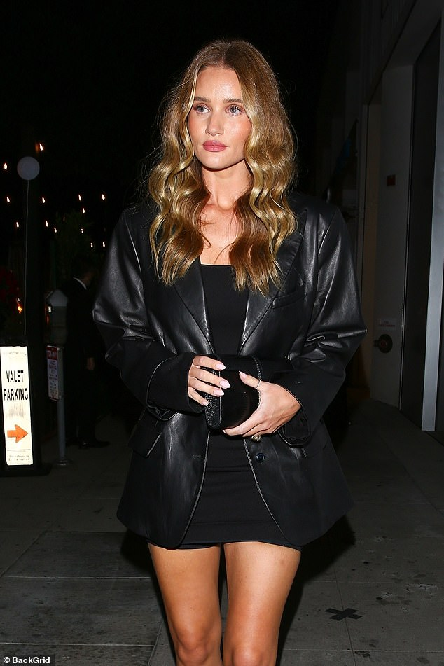 Stunning:The model, 34, ensured all eyes were on her as she left the restaurant in a black mini dress which she wore with a matching leather jacket