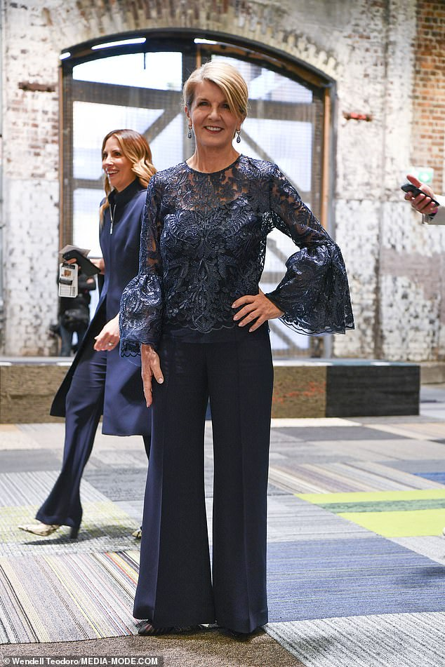 Stylish: Shewowed in a navy blue ensemble - a lace top with bell sleeves above a matching singlet top beneath, teamed with flared trousers and a pair of heels