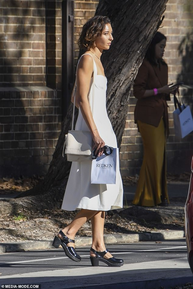 Goodies: She carried a small shopping bag on one arm, as well as an off-white handbag