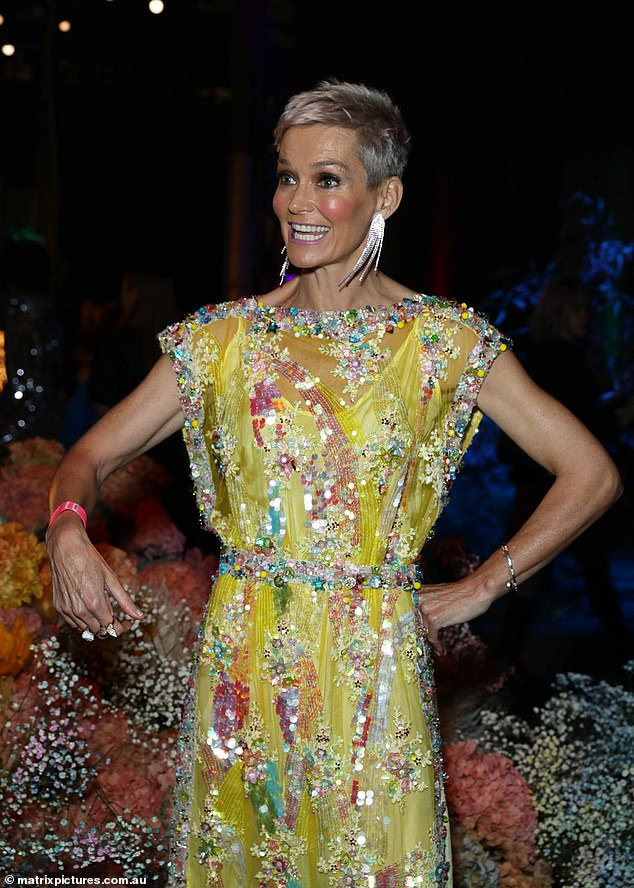 Show stopper:The TV star opted for statement earrings and a bright makeup palette including metallic purple lipstick