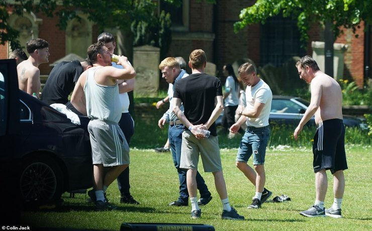 A group of men gather on Kew Green in West London yesterday as the travellers refuse to leave amid a stand-off with the council