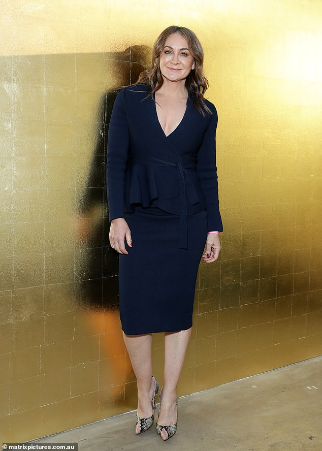 Looking good:The mother-of-one wore a black, long-sleeved top which clung close to her physique and ruffled at the waist