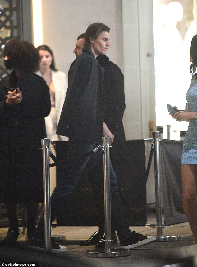 Heading back in: Jack draped a black jacket over his shoulders as he walked past Lauren