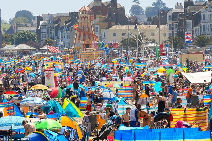 Sunbathers and holidaymakers flock to the beach at the seaside resort of Weymouth in Dorset this afternoon