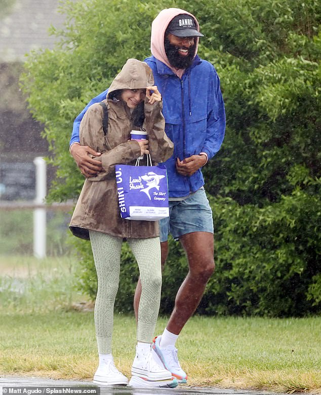 Appropriate attire: The former Bachelor star was dressed in a blue rain jacket that was worn on top of a light pink hoodie