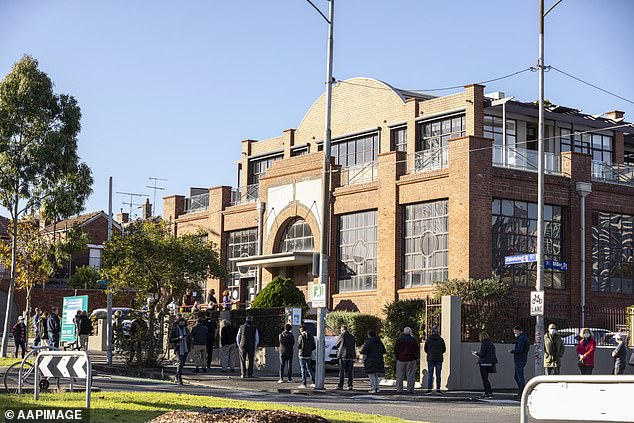 Dozens of people line up outside a COVID vaccination centre in West Melbourne on Monday