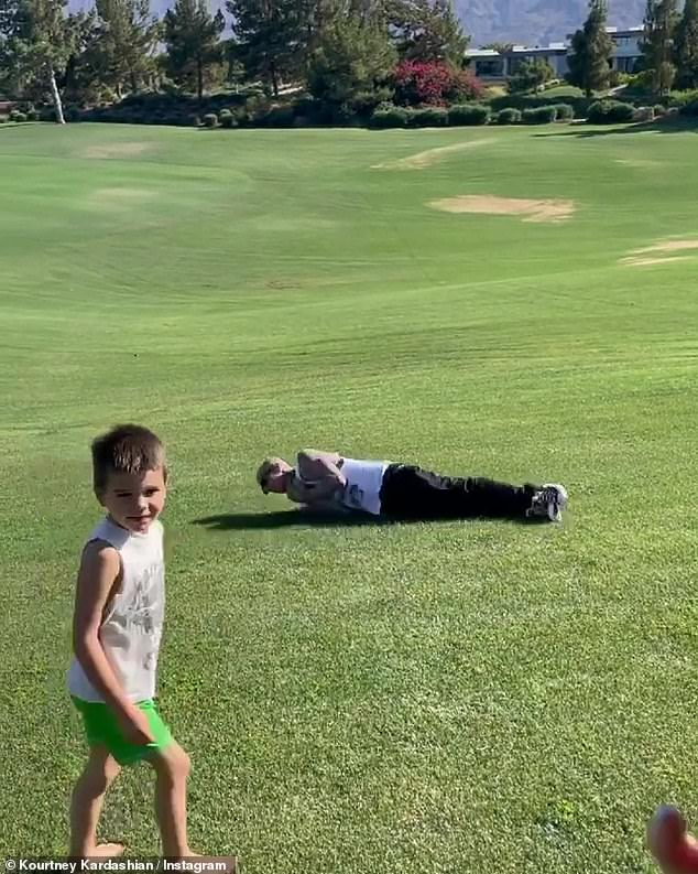 Fun times: The Blink-182 drummer could be seen climbing up the inflatable slide as he raced against Reign as Kourtney's eight-year-old daughter, Penelope, watched from the side