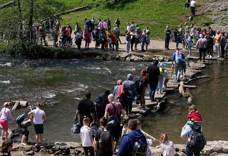 People queue to use the stepping stones over the River Dove during warm weather at Dovedale in the Peak District yesterday