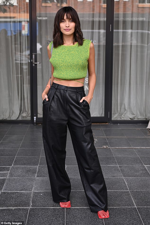 Green with envy:On Tuesday, the brunette, who was previously blonde, stunned as she attended the Albus Lumen show in a green and yellow wool crop top and leather trousers