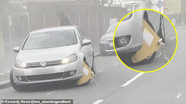 This is the moment a motorist attempts to drive off with a wheel clamp attached to his Golf