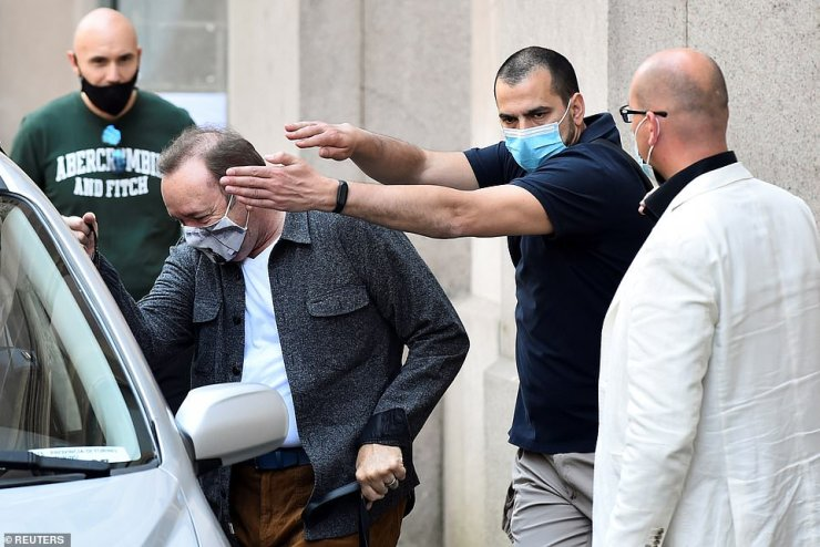 A companion tried to shield the Hollywood star's face as he got into the car after a private visit of the historic building Mole Antonelliana