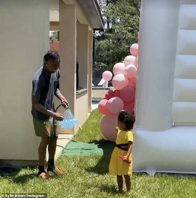 Playful:Over the weekend Travis and Kylie were seen playing with Stormi in a back yard. At one point Travis took a water balloon and playfully threw it at the younger sister of Kendall Jenner