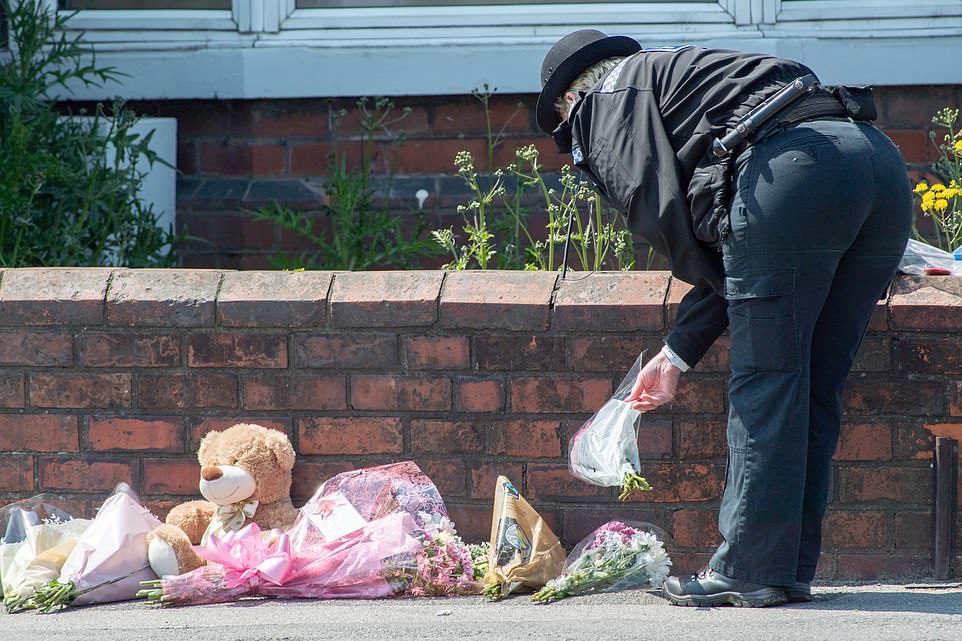 A police officer places a tribute at the scene where a 26-year-old mother and her son were found dead on Monday