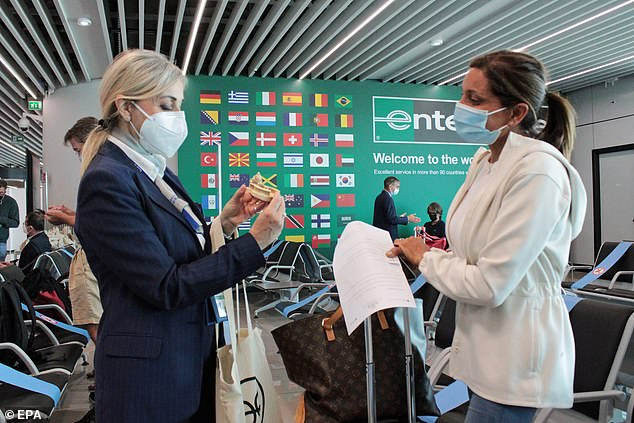 With vaccine passports, Americans may have to prove their vaccine status to certain businesses like restaurants and entertainment venues in order to be served without masks or social distancing. Pictured: A US tourist is screened atFiumicino Airport in Rome, May 28
