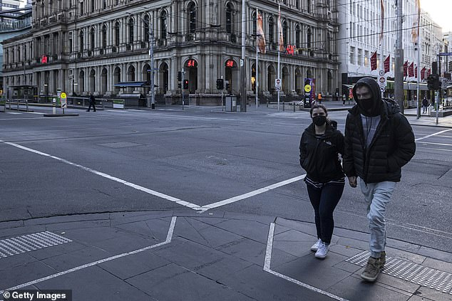 The cluster, which has been linked to a highly infectious double mutant Indian strain, grew to 60 cases on Wednesday (pictured, a couple in an eerily quiet Melbourne on Tuesday)