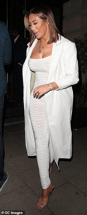 Chic: Chloe later changed into a new chic ensemble which included a white sparkly jumpsuit and matching duster coat