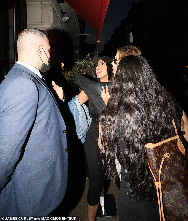 Commotion:Anna Vakili [second left] and her sister Mandi [second right] looked worse for wear on Tuesday night as they appeared to have a heated exchange with a security guard before seemingly being refused entry to Bethan Kershaw's fashion launch party at London's Novikov restaurant