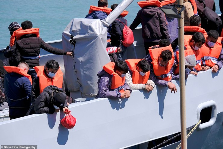Migrants arrive at the Kent coast after being brought into Britain by a Border Force cutter yesterday