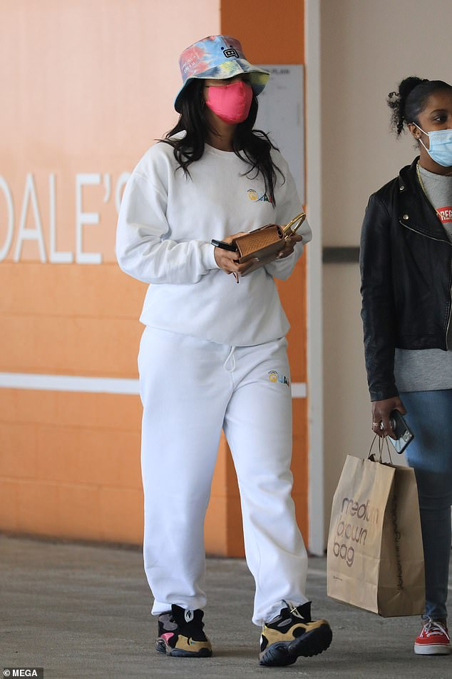 Relaxed fit: Kelly Rowland kept things casual on Wednesday in a white tracksuit and marble print bucket hat as she went shopping in Beverly Hills