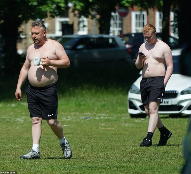 Two shirtless men walk on the grass at Kew Green in West London yesterday as the travellers continue to stay at the site