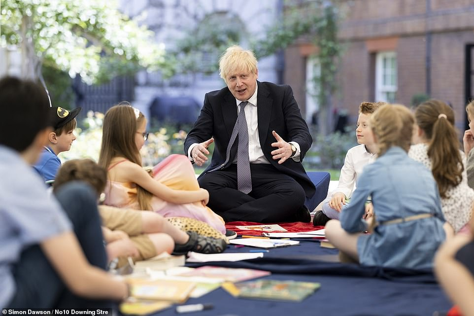 Boris Johnson warned that the government will have 'no hesitation' about imposing tougher restrictions ahead of a review of the allocations due tomorrow. He is pictured today holding a reception for school children in the garden of 10 Downing Street