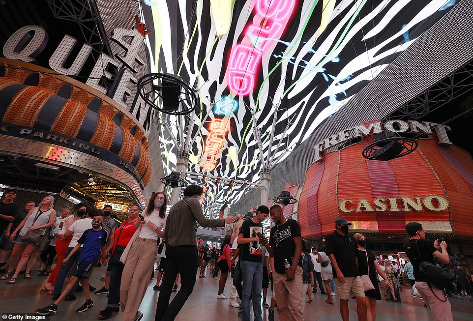 Visitors walk by the Four Queens Hotel & Casino and the Fremont Hotel & Casino under the Viva Vision canopy attraction at the Fremont Street Experience on May 31, just before restrictions in the city were officially dropped