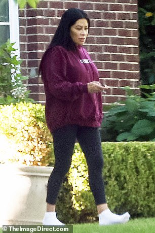 Cozy: The 47-year-old reality star opted for a maroon sweatshirt and leggings while strolling around her compound wearing socks