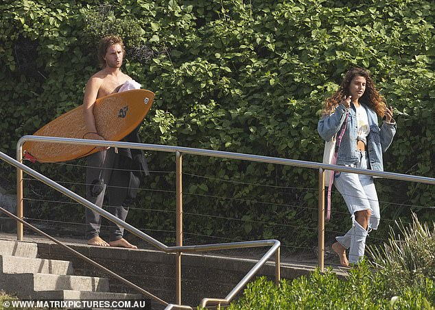 Letting her hair down!As they got closer to the water, Manon swap her tank for a white T-shirt knotted at the front, let her hair down and slipped into an oversized denim jacket