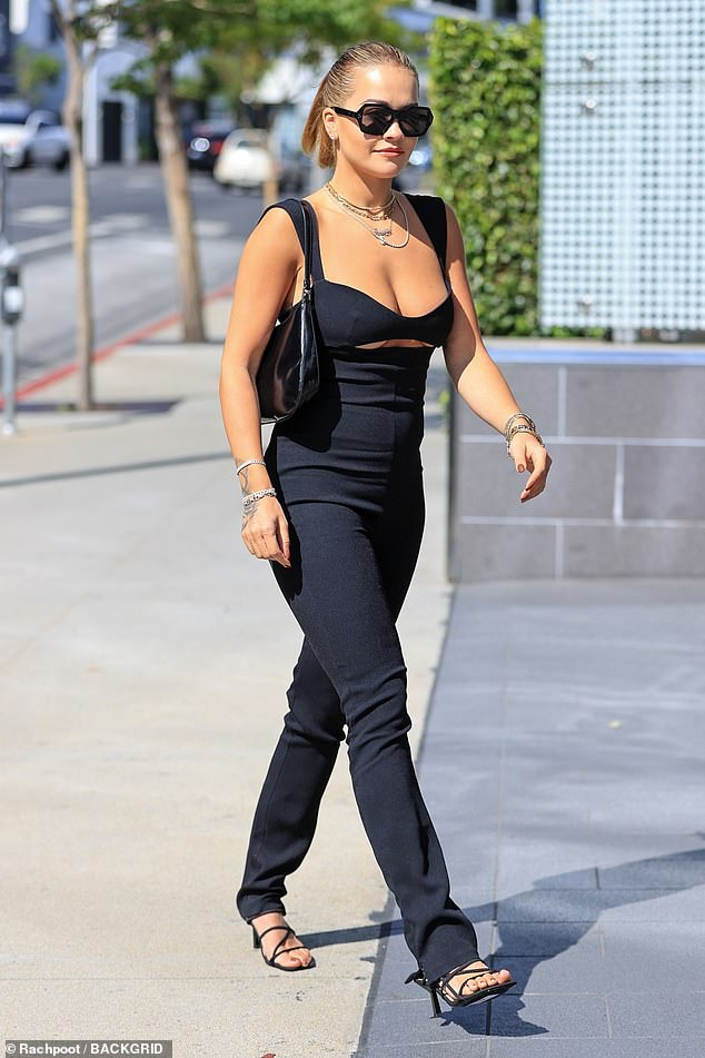 Out and about: The singer, 30, wore her hair slicked back from her face and sported octagonal sunglasses. She stepped out in strappy sandals and carried a black purse over her shoulder