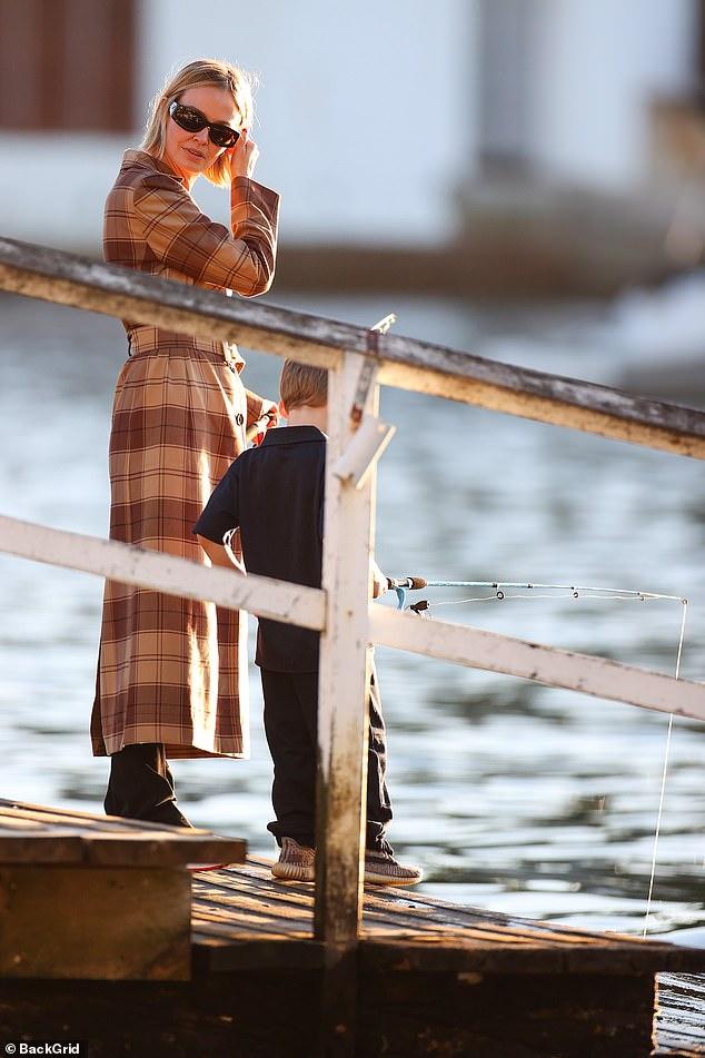 Family time! Lara Bingle cut a chic figure in a designer coat as she took her children fishing in Sydney