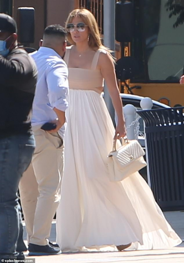 Flowing in the breeze:J Lo appeared to be wearing a dress, consisting of a beige bodice top with straps attached to a billowing white skirt