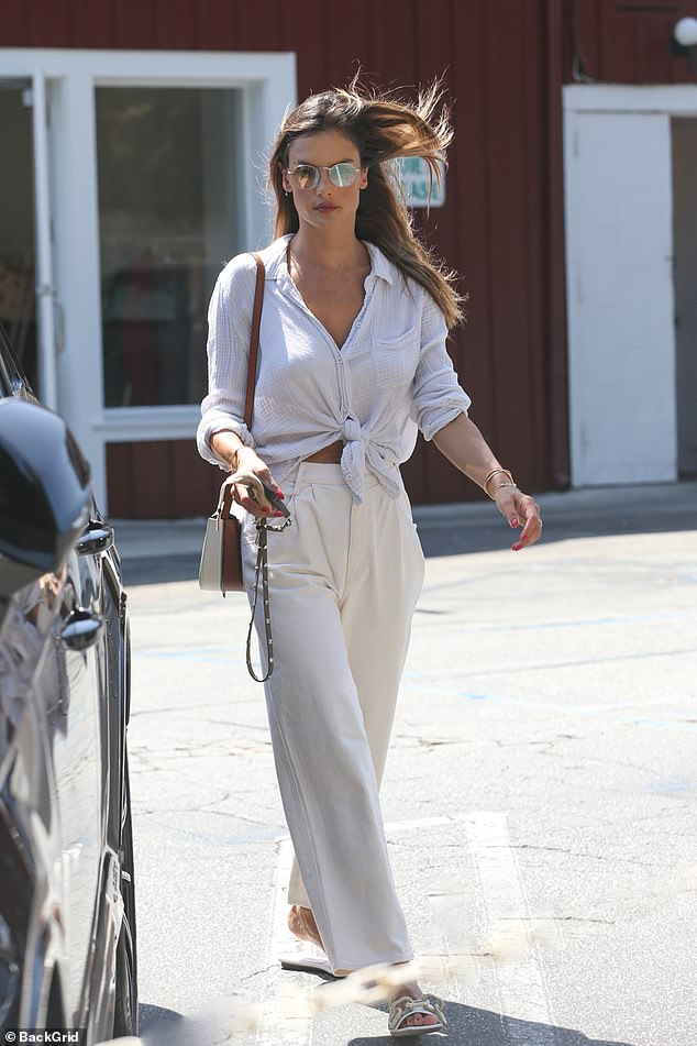 Sophisticated: The 39-year-old CAA Model looked chic in a cinched grey blouse with white pleated pants, matching purse, and sandals