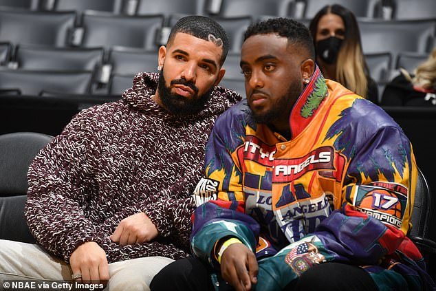With a friend inside the venue:The rapper, 34, looked characteristically stylish, in a brown and white knit oversized sweater and light chino pants