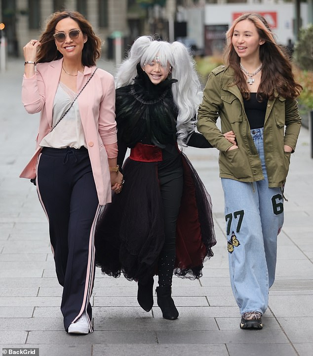 Attention to detail: Myleenestepped out in a pair of white trainers and kept her personal items in a black pleated handbag, while she accessorised with chic shades