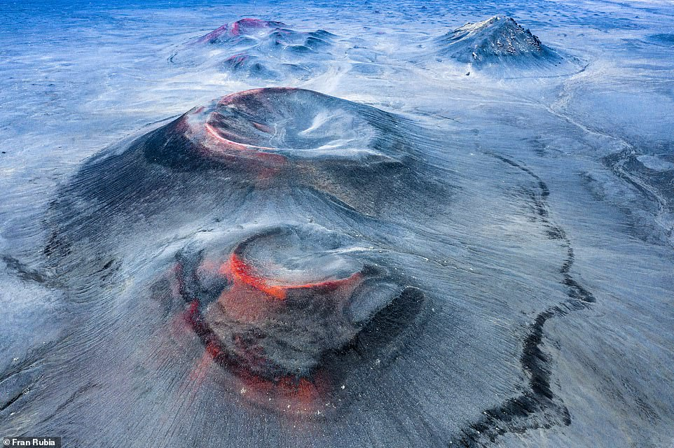 This jaw-dropping shot was declared the winner of theLandscapes, Waterscapes, and Flora category. It was taken byFran Rubia,a Spanish electrician who has studied photography through the Centro Andaluz de la Fotografía. The image was snapped via drone at the Fjallabak Nature Reserve in Iceland. bioGraphic said: 'What looks at first glance to be lava flowing down the sides of these Icelandic volcanoes is, in fact, iron oxide deposited during past eruptions. Unlike Geldingadalir, a volcano just 20 minutes away from Reykjavík that has been actively erupting since March 19, 2021, the last eruption here in FjallabakNature Reserve took place in 1480'