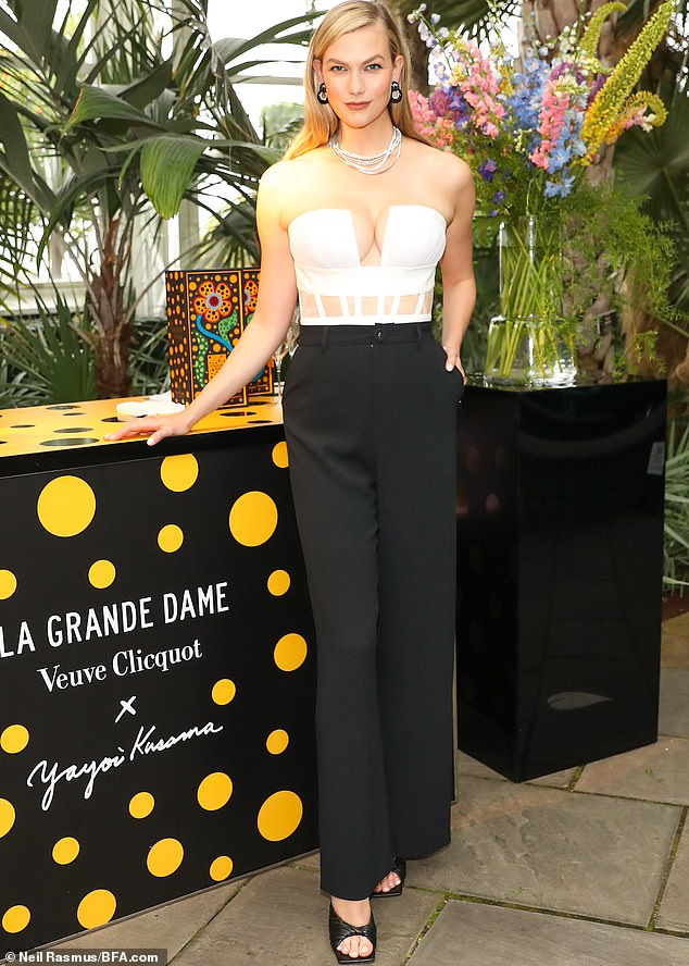 Swanking about:Karlie emphasized her cleavage in a plunging strapless white top that clashed elegantly against her black slacks