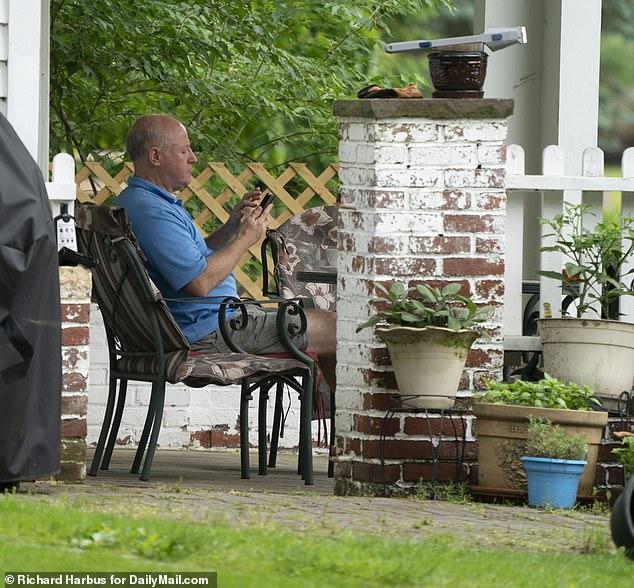 Vêtu d'un polo bleu, d'un short et de sandales, il s'est rendu sur le porche de la maison surplombant les montagnes de Ramapo, s'est assis et a commencé à agiter les bras avec une colère apparente alors qu'il avait une conversation animée sur son téléphone.