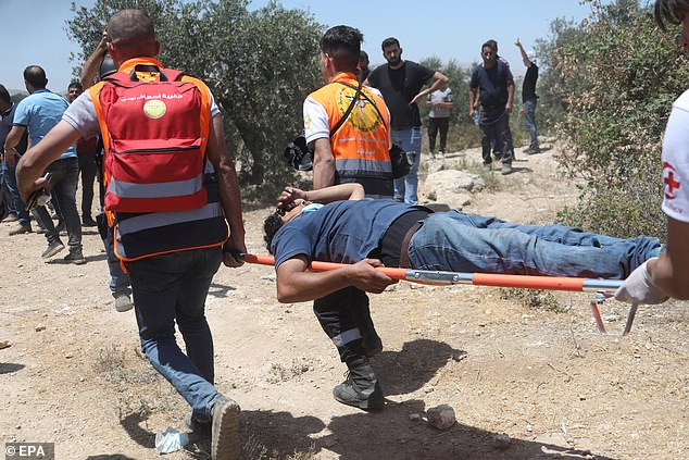Palestinian medics evacuate a wounded man during clashes with Israeli troops after a protest against a new Israeli settelment built over Palestinian lands near Beita village, near the West Bank City of Nablus, 04 June 2021
