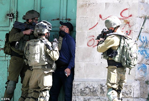 Israeli army soldiers arrest a Palestinian following scuffles during clashes with Palestinian stone throwers in the West Bank city of Hebron, 04 June 2021. Clashes erupted after the weekly Friday prayer