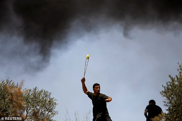 A Palestinian demonstrator uses a sling to hurl stones at Israeli forces during a protest against Israeli settlements in Beita, in the Israeli-occupied West Bank June 4, 2021