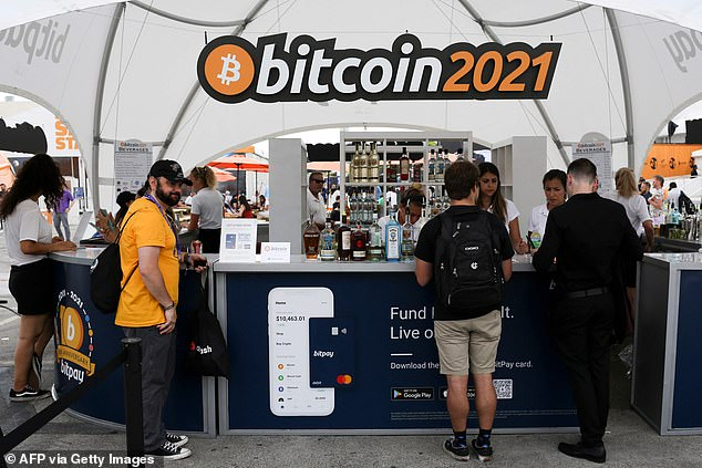 The logo of the crypto-currency conference Bitcoin 2021 Convention hangs above people buying drinks at a stand at the Mana Convention Center in Miami, Florida, on Friday