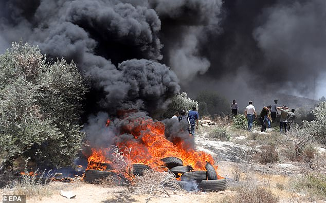 Palestinian protesters throw stones during clashes with Israeli troops after a protest against a new Israeli settelment built over Palestinian lands near Beita village, near the West Bank City of Nablus, 04 June 2021