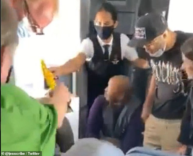 Another member of the flight crew is pictured handing the yellow zip ties off to someone else on the flight as Williams and two other passengers detain him on the ground