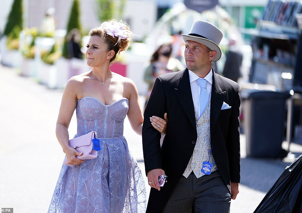 Purple perfection: Another racegoer opted for a lace sheet strapless number and pink clutch bag which while her partner sported a baby blue tie