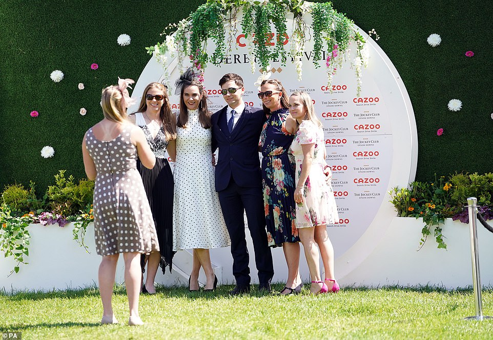 Glammed up and ready to go: One group of glamorous ladies surrounded a man at Epsom today